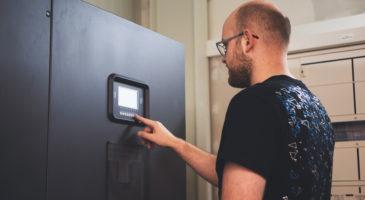 Mitarbeiter bedient Gerät zur Überwachung der Stromversorgung.