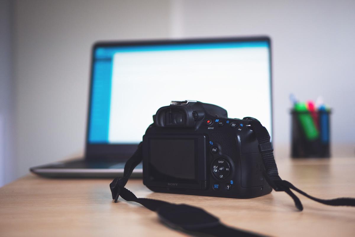 Kamera liegt vor Laptop auf Schreibtisch.