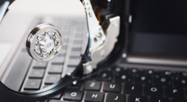 Eine Festplatte liegt auf der Tastatur eines Laptops.